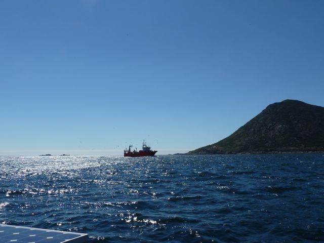 een vissertje komt met ons binnenvaren in de baai