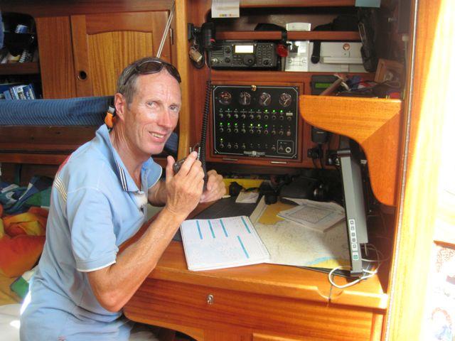 Pieter bezig met het radiorondje, leuk om de belevenissen van andere zeilers te horen