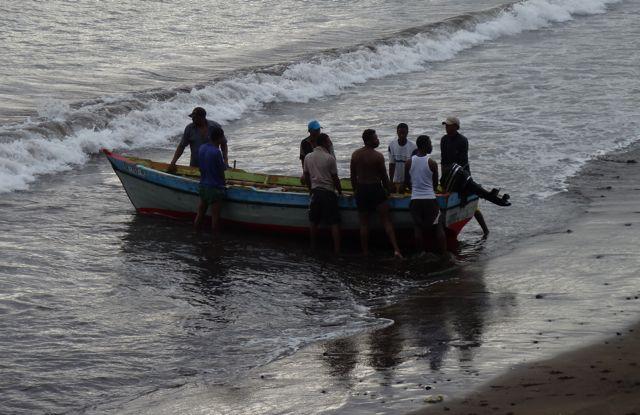 De visserssloep komt aan, binnen een paar minuten staan 20 mannen klaar om hem aan land te helpen trekken.