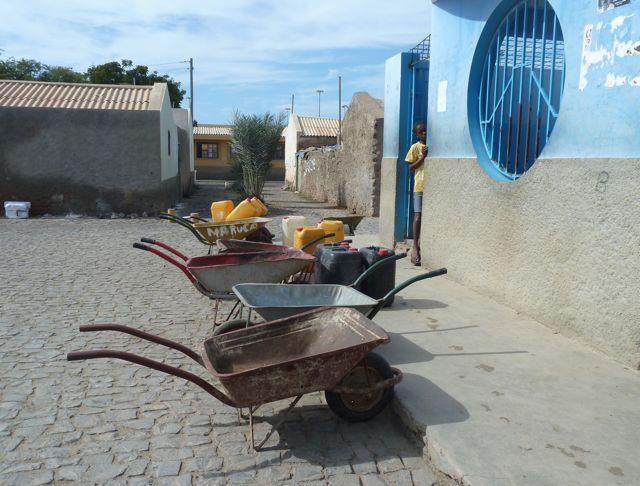het waterhuis; iedereen haalt hier dagelijks in grote jerrycans het water voor het huishouden