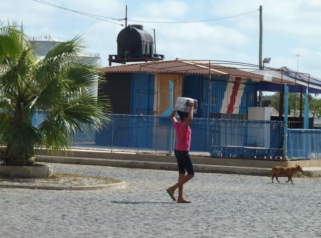 Iedereen draagt z'n spullen op het hoofd, het geeft sfeer aan het straatbeeld