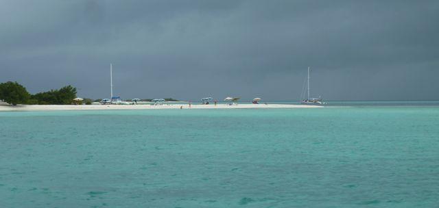 1 keer dreigende luchten, de toeristen zitten onder parasolletjes op het witte strand